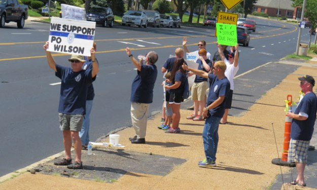 Supporters of Police Officer Darren Wilson gather outside a local bar to greet traffic and raise money for Wilson.